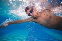 De jonge mens die de voorzijde zwemmen kruipt in een pool Stock Afbeeldingen