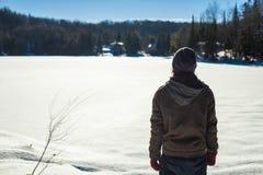 De jonge mens die een tuque dragen overweegt de horizon stock foto