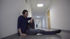 De jonge mens die in het ziekenhuisgang wachten, die hoop ervaren spit hebben stock videobeelden