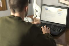De jonge mens die laptop in zijn bebouwde studieruimte met behulp van, en sluit omhoog royalty-vrije stock afbeelding