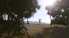 De jonge mens die met rugzak langs tropisch strand lopen bereikt oceaan en het opheffen van wapens Mannelijke wandelaar die bij z Stock Afbeeldingen