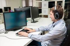 De jonge mens die oortelefoons dragen zit in het bureau met computer Royalty-vrije Stock Foto's