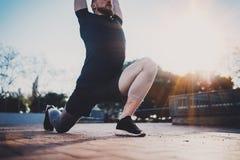 De jonge mens die rek doen oefent spieren uit alvorens op te leiden Het concept van de traininglevensstijl Spieratleet die buiten royalty-vrije stock afbeelding