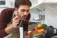 De jonge mens die romantisch diner koken proeft thuis soep royalty-vrije stock foto