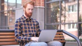 De Jonge Mens die van de roodharigebaard aan Laptop, Zitten werken Openlucht op Bank stock video