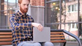 De jonge mens die van de roodharigebaard en op bank komen zitten om laptop te gebruiken stock videobeelden