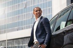 De jonge mens die zich dichtbij auto bevinden dient zakken in kijkend opzij peinzend zijaanzicht royalty-vrije stock foto