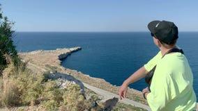 De jonge mens die zich op klip boven het overzees bevinden, neemt en werpt steen op Overzees Dolly binnen stock videobeelden