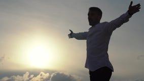 De jonge mens die zijn handenbyside werpen, die van vrijheid genieten, gelooft toekomstig succes Gelukkige toerist op rotsbovenka stock videobeelden