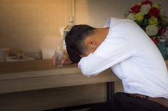 De jonge mens diepbedroefd in vrijetijdskleding slaapt dichtbij de fles Wodka op een barteller in bar royalty-vrije stock fotografie