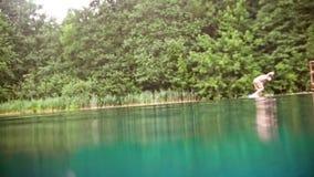 De jonge mens doet een tik in het water in het diepe blauwe DE-geconcentreerde meer - stock video