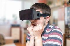 De jonge mens draagt 3D virtuele werkelijkheidsglazen en is doen schrikken Royalty-vrije Stock Foto