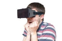 De jonge mens draagt 3D virtuele werkelijkheidsglazen en is doen schrikken Stock Foto's
