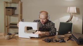 De jonge mens draagt hoofdtelefoons en luistert aan muziek Het werken als kleermaker en het gebruiken van een naaimachine in een  stock videobeelden