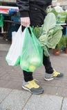 De jonge mens draagt zijn aankoop in plastic zakken van het weekblad in de war brengt stock afbeelding