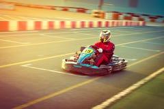 De jonge mens drijft gaat -gaan-kart auto met snelheid in een speelplaats het rennen spoor stock afbeelding