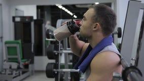 De jonge mens drinkt eiwitcocktail binnen in gymnastiek stock footage