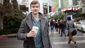 De jonge mens drinkt koffie op een zebrapad stock video