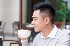 De jonge mens drinkt koffie op de straat De mens drinkt koffie De jonge Mens drinkt Koffie Openlucht De zakenman drinkt koffie op Royalty-vrije Stock Afbeeldingen