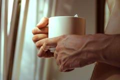 De jonge mens drinkt koffieochtend, de zomer, de herfst Het concept comfort, warmte, haard stock afbeeldingen