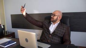 De jonge mens in een kostuum zit in het bureau en maakt een selfie Maakt grappige gezichten, dwazen rond, het verheugen zich Het  stock footage