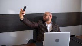 De jonge mens in een kostuum zit in het bureau en maakt een selfie Maakt grappige gezichten, dwazen rond, het verheugen zich Het  stock video