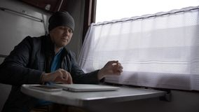 De jonge mens in een trein begint aan laptop te werken stock afbeelding