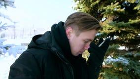 De jonge mens in een warm jasje en handschoenen controleert de aanrakingstelefoon met zijn neus en beantwoordt de vraag Het conce stock videobeelden