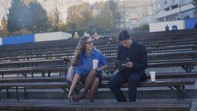 De jonge mens en de bedrijfsdame zitten op een bank in het park stock videobeelden