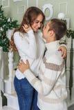 De jonge mens en een jong meisje bevinden zich op de witte treden in het huis, glimlachen en bekijken elkaar op de vooravond van  stock fotografie