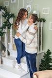 De jonge mens en een jong meisje bevinden zich op de witte treden in het huis, glimlachen en bekijken elkaar op de vooravond van  royalty-vrije stock fotografie