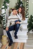 De jonge mens en een jong meisje zitten op de stappen van een witte trap in een huis in de vooravond van Nieuwjaarvakantie Meisje royalty-vrije stock fotografie