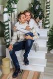 De jonge mens en een jong meisje zitten op de stappen van een witte trap in een huis in de vooravond van Nieuwjaarvakantie Het be stock foto's