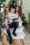 De jonge mens en een jong meisje zitten op de stappen van een witte trap in een huis in de vooravond van Nieuwjaarvakantie Meisje royalty-vrije stock foto's