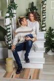 De jonge mens en een jong meisje zitten op de stappen van een witte trap in een huis in de vooravond van Nieuwjaarvakantie Meisje royalty-vrije stock afbeeldingen