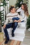De jonge mens en een jong meisje zitten op de stappen van een witte trap in een huis in de vooravond van Nieuwjaarvakantie Meisje stock foto's