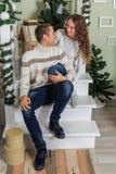 De jonge mens en een jong meisje zitten op de stappen van een witte trap in een huis in de vooravond van Nieuwjaarvakantie Meisje royalty-vrije stock foto
