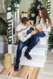 De jonge mens en een jong meisje zitten op de stappen van een witte trap in een huis in de vooravond van Nieuwjaarvakantie Kerell stock afbeeldingen