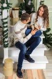 De jonge mens en een jong meisje zitten op de stappen van een witte trap in een huis in de vooravond van Nieuwjaarvakantie Kerell stock foto