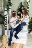 De jonge mens en een jong meisje zitten op de stappen van een witte trap in een huis in de vooravond van Nieuwjaarvakantie Kerell royalty-vrije stock afbeeldingen