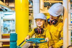 De jonge mens en een kleine jongen zijn allebei in het geel eenvormig werk, glazen, en helm in een industri?le omgeving, olie royalty-vrije stock afbeelding
