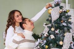 De jonge mens en het jonge meisje maken samen een Kerstboom op de vooravond van de Kerstmisvakantie in orde Close-up royalty-vrije stock fotografie