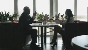 De jonge mens en het meisje zitten in het restaurant stock footage