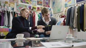 De jonge mens en zijn volwassen vrouwelijke partner bespreken hun project en onderzoeken grafiek stock footage
