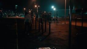 De jonge mens gaat van sportengrond uit in park bij nacht stock footage