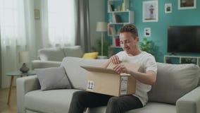 De jonge mens gaat zijn woonkamer met het pakket van de kartondoos in, begint het te openen stock videobeelden