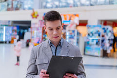 De jonge mens gebruikt tablet in winkel Royalty-vrije Stock Afbeelding