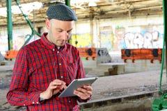 De jonge mens gebruikt zijn tabletpc Stock Fotografie