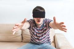 De jonge mens is gefascineerd van virtuele werkelijkheidshoofdtelefoon royalty-vrije stock afbeelding