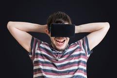 De jonge mens is gefascineerd van virtuele werkelijkheidshoofdtelefoon stock afbeeldingen